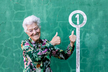 Happy Aged Gray Haired Female In Colorful Blouse Standing Against Green Wall And Pointing At Number 1 Sign On Parking Lot