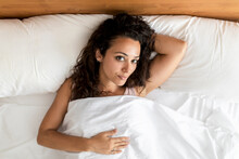 Top View Of Delighted Female Lying On Bed Looking At Camera After Awakening In Bedroom In Morning