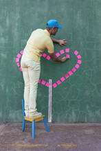 Side View Of African American Male Standing On Chair And Making Heart From Pink Sticky Notes