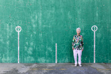 Full Body Of Elegant Elderly Female In Stylish Outfit Standing Against Green Wall With Numbers On Parking Lot