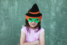 Calm Child Wearing Creative Costume Of Witch Standing On Street Looking At Camera At Halloween