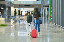 Back View Of Anonymous Women Carrying Luggage In Contemporary Airport With Waiting Room