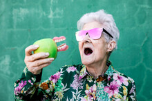Stylish Elderly Female In Trendy Outfit And Sunglasses Holding Green Apple With Denture While Standing Against Green Background