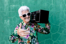 Happy Elderly Gray Haired Female In Stylish Outfit Carrying Record Player On Shoulder While Standing Against Green Wall On Street Looking At Camera