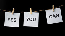 Words Of Yes You Can On White Stickers Hanging By A Rope Against Black Background.