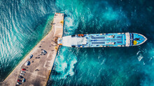 Aerial Drone View Of Departing Ferry At Port With Beautiful Crystal Blue Water. Luxury Cruise On A Sunny Day Greece. People And Cars Waiting In The Harbour. Docking Ship.