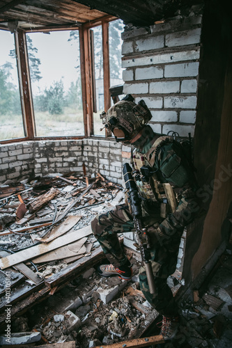 Tablou Canvas Military man with assault rifle standing inside building, he is ready for combat