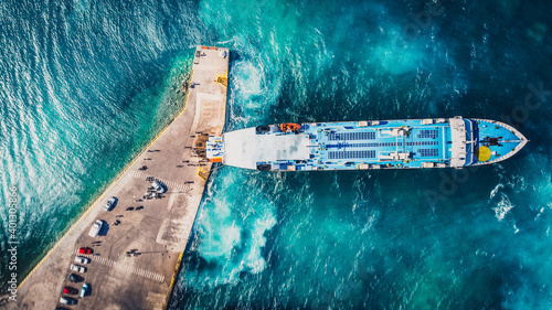 Slika na platnu Aerial drone view of departing ferry at port with beautiful crystal blue water