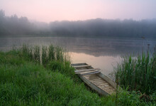 Wooden Boat On The Lake On A Foggy Autumn Morning.