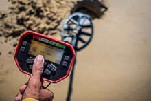 Treasure Hunter Use Metal Detector To Find Valuable Items Buried In The Sand