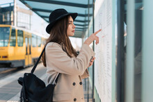 Woman Tourist At Bus Stop Looking On Map Of Public Transport Routes