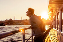 A Young Travelling Man On A Ferry Floats To The Shores Of Istanbul, Turkey In The Rays Of Sunset. The Beginning Of A Great Adventure.