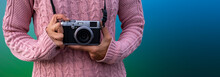 Photographer  With A Vintage Camera In Her Hands And Graduated Blue And Green Background