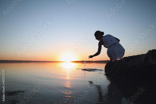 Foto Woman near river on sunset. Healing concept