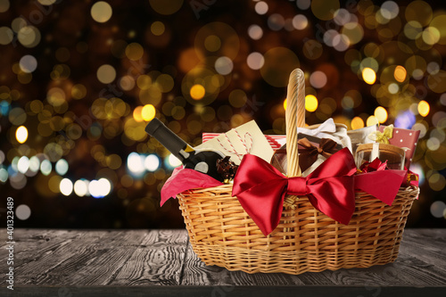Fotografía Wicker basket full of gifts on wooden table against blurred festive lights