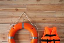 Orange Life Jacket And Lifebuoy On  Wooden Background. Rescue Equipment