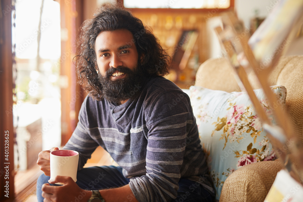 Fototapeta Bearded young man holding cup of coffee at home