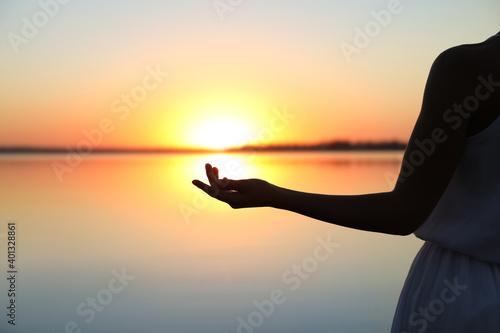 Canvas Woman near river on sunset, closeup. Healing concept