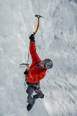 Alpinist man with ice tools axe climbing a large wall of ice. Outdoor Sports Portrait.