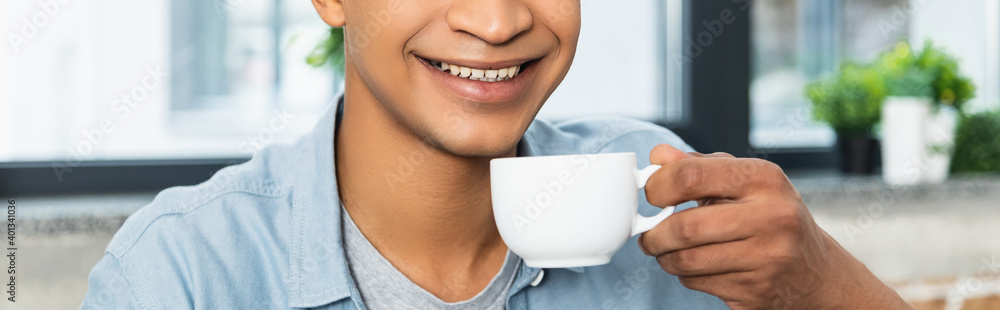 Fototapeta cropped view of young african american man holding cup of coffee, banner.