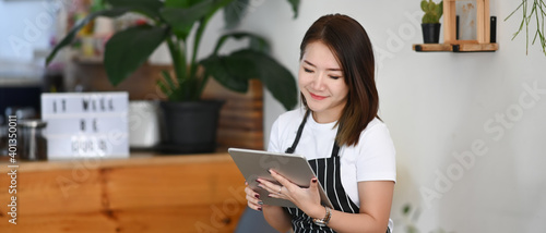 Fototapeta Horizontal photo of  successful small business owner woman sitting in her coffee shop and using digital tablet. obraz