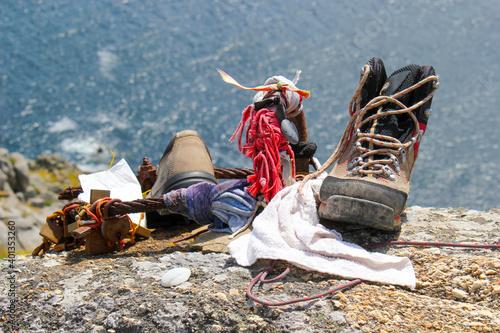 Fotografering Botas de trekking sobre un acantilado en el final del Camino de Santiago