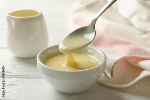Fototapeta Kitchen towel and bowls with condensed milk on wooden background obraz
