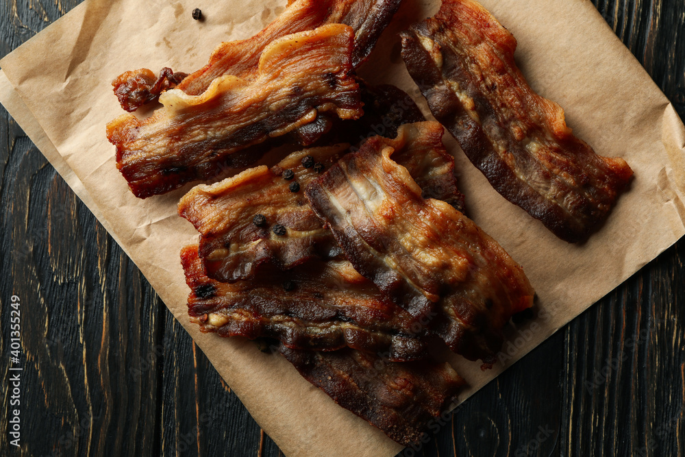 Fototapeta Baking paper with fried bacon on wooden background