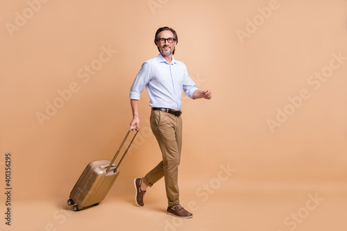 Full length body size view of nice classy cheerful man going departure carrying bag isolated over beige pastel color background