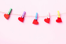 Happy Valentine's Day Concept. Red Heart-shaped Valentines Decoration Hanging With Wood Clips For Love On The Rope Isolated On Pink Background With Copy Space