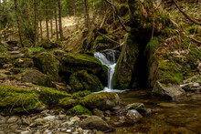 Little Waterfall Over Green Rocks In The Forest