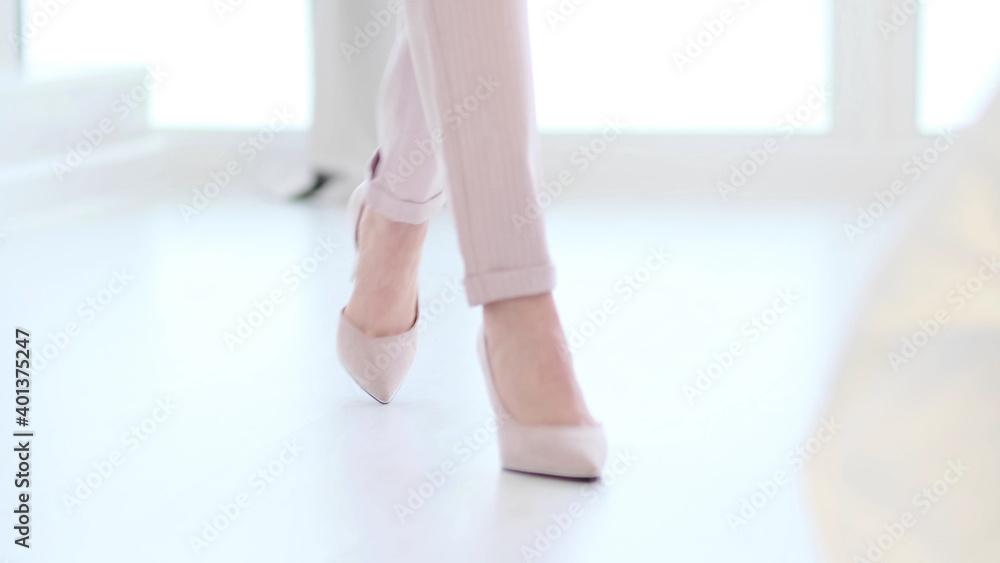 Fototapeta Fashionable woman wearing high heel shoes. Fashionable woman in high-heeled shoes. soft focus woman walking on white wooden floor.