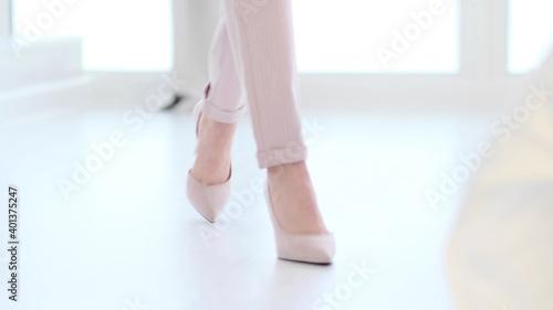 Obraz Fashionable woman wearing high heel shoes. Fashionable woman in high-heeled shoes. soft focus woman walking on white wooden floor. - fototapety do salonu