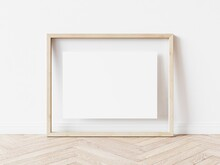 Rectangular Wooden Picture Frame With Thin Light Border And White Background Standing On Wooden Floor. 3D Illustration.