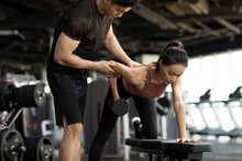 Young Woman Working Out With Personal Trainer At Gym