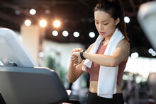 Young Woman Checking Smart Watch At Gym