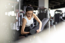 Young Woman Working Out With Dumbbell At Gym