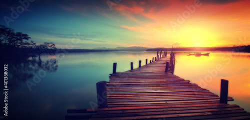 Obraz Wooden Jetty at Sunset - Dreamy Looks . Aerial bird's eye drone photo of state of the art suspension bridge crossing the sea .Wooden bridge over lake in early misty morning  - fototapety do salonu