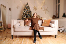 Young Woman In A Festive Living Room Sitting On A Couch On A Christmas Eve Near The Christmas Tree And Lights Ready To Open Presents