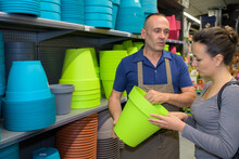 Shop Assistant Helping Customer With Plant Pots In Garden Center