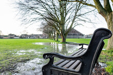 Close-up Of A Park Bench Seen Within A Community Park. Taken After A Heavy Storm, The Nearby Fields Are Waterlogged After Heavy Rain.