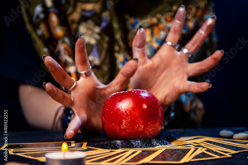 Obraz na plátne A fortune teller conjures a red apple lying on the Tarot cards