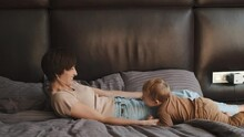 Childhood, Mother's Loe Concept. Happy Kid And Mother Are Together At Home. The Boy Is Having Fun With Mother Laying In Bed.