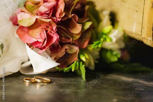Fotografering Anelli nozze appoggiati su tavolo di legno con bouquet