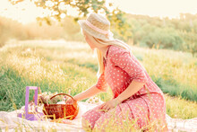 Beautiful Girl In A Pink Dress And A Straw Hat On A Picnic In A Spring Park. A Woman Sits On A Blanket In A Meadow With Lush Grass.