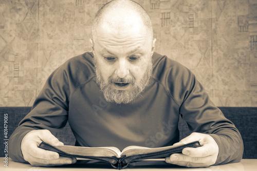Fototapeta happy bearded man studies the Bible. religion and Christianity.