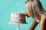 Portrait of young sexy blonde woman standing on all fours and licking big cake with cream and candle over blue background. Side view. Figure, present, birthday party concept