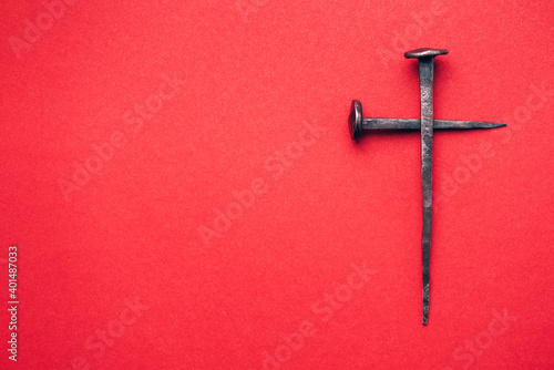 Fotografie, Obraz Cross made with rusty nails and drops of blood on red background