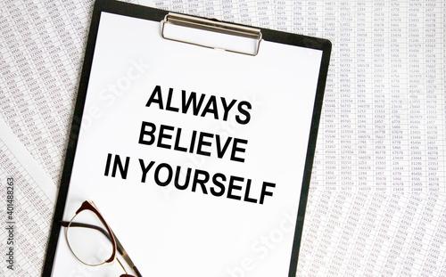 Fototapeta On the tablet for writing the teakst ALWAYS BELIEVE IN YOURSELF, next to the glasses, the background are reports