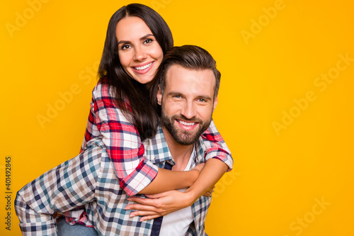 Canvas Print Photo portrait of woman riding on man's back isolated on vivid yellow colored ba